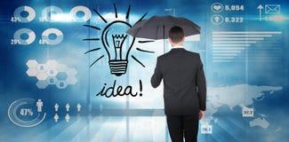 Zusammengesetztes Bild des Geschäftsmannes schützend unter schwarzem Regenschirm Stockbild