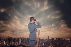Zusammengesetztes Bild des Geschäftsmannes schauend auf einer Leiter Stockfotografie