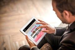 Zusammengesetztes Bild des Geschäftsmannes unter Verwendung der Tablette Stockbild