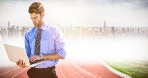 Zusammengesetztes Bild des Geschäftsmannes unter Verwendung eines Laptops lizenzfreie stockfotos