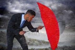 Zusammengesetztes Bild des Geschäftsmannes verteidigend mit rotem Regenschirm Lizenzfreies Stockfoto