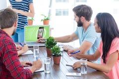 Zusammengesetztes Bild des Geschäftsteams unter Verwendung eines Laptops Stockbilder