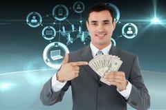 Zusammengesetztes Bild des Geschäftsmannes zeigend auf Banknoten in seiner Hand Lizenzfreies Stockfoto