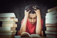 Zusammengesetztes Bild des gestrafften Jungen, der mit Stapel Büchern sitzt Lizenzfreies Stockbild