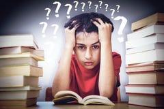 Zusammengesetztes Bild des gestrafften Jungen, der mit Stapel Büchern sitzt Lizenzfreie Stockfotos