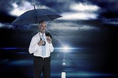 Zusammengesetztes Bild des glücklichen Geschäftsmannes Regenschirm halten Lizenzfreie Stockfotos
