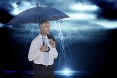 Zusammengesetztes Bild des glücklichen Geschäftsmannes Regenschirm halten Lizenzfreie Stockfotografie
