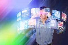 Zusammengesetztes Bild des glücklichen jungen Mannes, der virtuelle Videogläser verwendet Stockbild