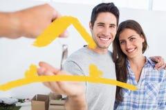 Zusammengesetztes Bild des glücklichen Mannes, der einen Hausschlüssel gegeben wird Lizenzfreie Stockfotos
