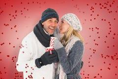 Zusammengesetztes Bild des glücklichen Paars auf die Wintermode, die Becher hält Lizenzfreie Stockbilder
