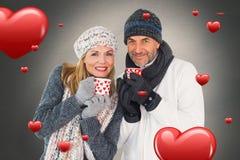 Zusammengesetztes Bild des glücklichen Paars auf die Wintermode, die Becher hält Lizenzfreie Stockfotos
