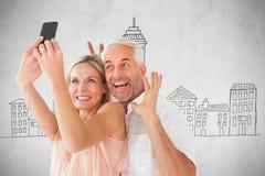 Zusammengesetztes Bild des glücklichen Paars aufwerfend für ein selfie Lizenzfreie Stockfotografie