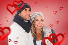 Zusammengesetztes Bild des glücklichen Paars bei der Wintermodeumfassung Stockbilder