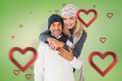 Zusammengesetztes Bild des glücklichen Paars bei der Wintermodeumfassung Lizenzfreie Stockfotografie