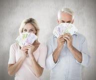 Zusammengesetztes Bild des glücklichen Paars blitzend ihr Bargeld Lizenzfreie Stockfotografie