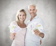 Zusammengesetztes Bild des glücklichen Paars blitzend ihr Bargeld Stockfotos