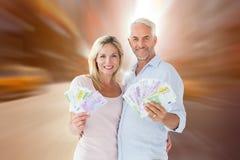 Zusammengesetztes Bild des glücklichen Paars blitzend ihr Bargeld Stockbild
