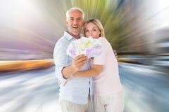 Zusammengesetztes Bild des glücklichen Paars blitzend ihr Bargeld Stockbilder