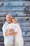 Zusammengesetztes Bild des glücklichen Paars blitzend ihr Bargeld Lizenzfreies Stockfoto
