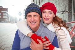 Zusammengesetztes Bild des glücklichen Paars in der warmen Kleidung Lizenzfreie Stockfotografie