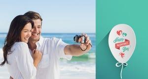 Zusammengesetztes Bild des glücklichen Paars ein Foto machend Stockfoto
