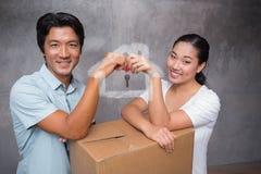 Zusammengesetztes Bild des glücklichen Paars Hausschlüssel halten und auf beweglichem Kasten lehnend Stockbild