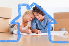 Zusammengesetztes Bild des glücklichen Paars ihr neues Haus organisierend Lizenzfreie Stockfotos