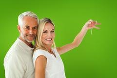 Zusammengesetztes Bild des glücklichen Paars ihren Schlüssel des neuen Hauses zeigend Lizenzfreie Stockfotos
