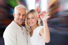 Zusammengesetztes Bild des glücklichen Paars ihren Schlüssel des neuen Hauses zeigend Lizenzfreies Stockbild