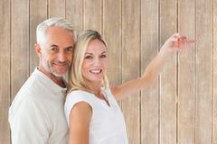 Zusammengesetztes Bild des glücklichen Paars ihren Schlüssel des neuen Hauses zeigend Lizenzfreie Stockbilder