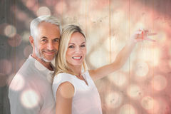 Zusammengesetztes Bild des glücklichen Paars ihren Schlüssel des neuen Hauses zeigend Stockbilder