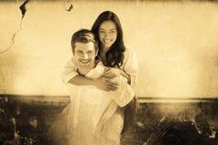 Zusammengesetztes Bild des glücklichen Paars lächelnd an der Kamera Lizenzfreies Stockbild