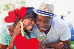 Zusammengesetztes Bild des glücklichen Paars liegend im Garten, der zusammen Musik hört Lizenzfreies Stockfoto