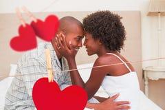 Zusammengesetztes Bild des glücklichen Paars Neigung auf Bett zeigend lizenzfreie abbildung