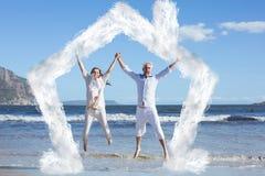 Zusammengesetztes Bild des glücklichen Paars oben barfuß springend auf den Strand Lizenzfreies Stockfoto