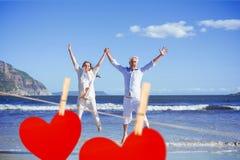 Zusammengesetztes Bild des glücklichen Paars oben barfuß springend auf den Strand Stockbilder