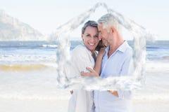Zusammengesetztes Bild des glücklichen Paars umarmend auf der Strandfrau, die Kamera betrachtet Stockfotos