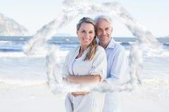 Zusammengesetztes Bild des glücklichen Paars umarmend auf der Strandfrau, die Kamera betrachtet Lizenzfreie Stockfotos