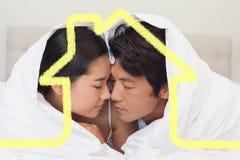 Zusammengesetztes Bild des glücklichen Paars zusammen liegend auf Bett unter der Daunendecke Lizenzfreie Stockfotos