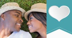 Zusammengesetztes Bild des glücklichen Paars zusammen liegend im Garten Stockbild