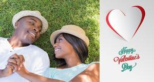 Zusammengesetztes Bild des glücklichen Paars zusammen liegend im Garten auf dem Gras Stockbilder