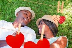 Zusammengesetztes Bild des glücklichen Paars zusammen liegend im Garten auf dem Gras Lizenzfreie Stockfotografie