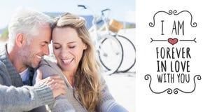 Zusammengesetztes Bild des glücklichen Paars zusammen sitzend auf dem Sand Lizenzfreie Stockfotos