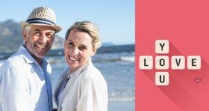 Zusammengesetztes Bild des glücklichen Paars zusammen stehend auf dem Strand Stockfoto