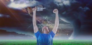 Zusammengesetztes Bild des glücklichen Rugbyspielers, der Trophäe 3D hält Stockfoto