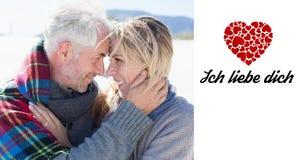 Zusammengesetztes Bild des glücklichen verheirateten Paars umfassend auf dem Strand Stockfotografie