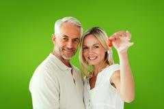 Zusammengesetztes Bild des glücklichen Paars ihren Schlüssel des neuen Hauses zeigend Lizenzfreie Stockfotografie