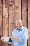 Zusammengesetztes Bild des glücklichen reifen Mannes, der auf seinen Tabletten-PC zeigt Lizenzfreie Stockbilder