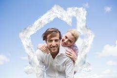Zusammengesetztes Bild des gutaussehenden Mannes piggyback gebend seiner Freundin Stockbilder