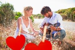 Zusammengesetztes Bild des gutaussehenden Mannes seine Freundin mit Gitarre ein Ständchen bringend Stockfoto